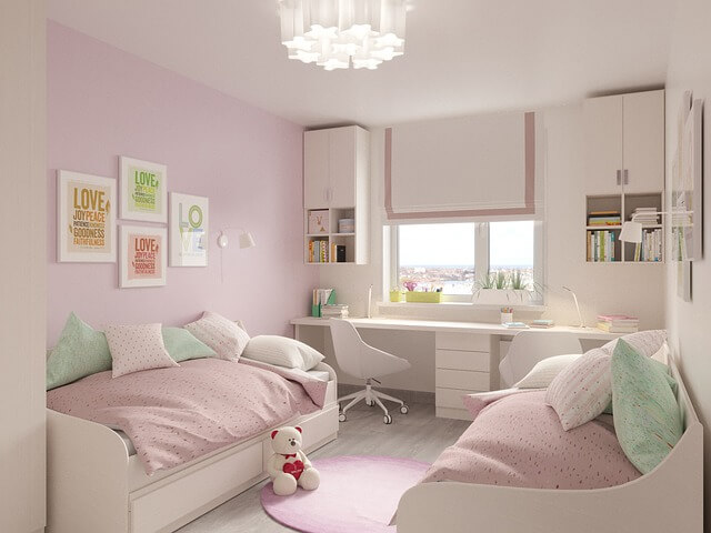 różowe i białe meble dla dzieci w niewielkim jasnym pokoiku z oknem pod którym stoją dwa białe biurka z białymi krzesłami i pastelowymi dodatkami takimi jak segregatory i książki a po dwóch stronach przy ścianach znajdują się dwa białe łóżka z różowym nakryciem i kolorowymi poduszkami, gdzie przy jednym łóżku leży biały miś z serduszkiem a na ścianach wiszą kolorowe obrazki z napisem love