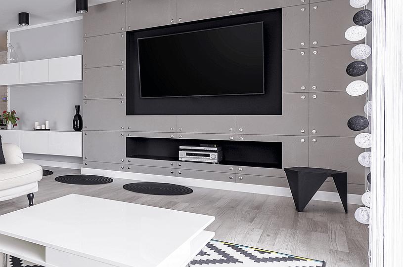 alarm domowy w jasnym dużym pokoju z białą sofą i dużym telewizorem na szarej ścianie zbudowanej z prostokątnych modułów ścianie