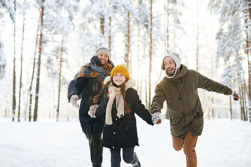 Bezpieczna zima, czyli dziewczynka w ciemnej kurtce i żółtej czapce biegnie przez zimowy las ciągnąć lewą ręką mężczyznę w zielonej kurtce i białej czapce, a w prawej dłoni trzymając rękę kobiety w ciemnej puchowej kurtce z kraciastym szalikiem
