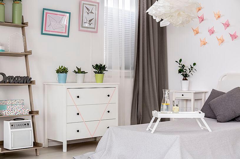 Dekoracje do domu do jasnego pokoju czyli sypialnia z białymi ścianami, komodą, łóżkiem z szarymi poduszkami i szarymi zasłonami oraz kolorowe obrazki i papierowe motyle na ścianach