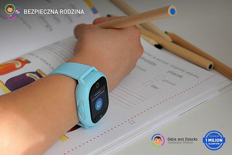 Domowa kwarantanna, sprawdzanie, co robi dziecko, czyli ręka chłopca z niebieskim zegarkiem z GPS od Bezpiecznej Rodziny ułożona na otwartym zeszycie wśród kolorowych kredek