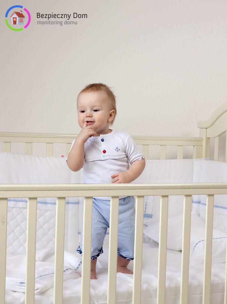 Małe dziecko stojące w łóżeczku