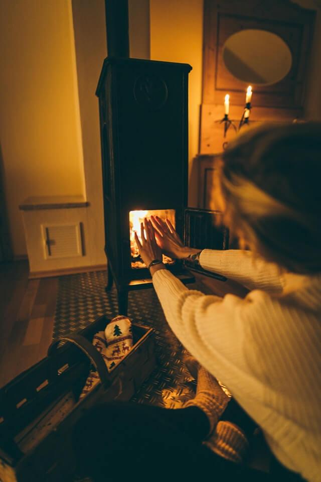 młoda kobieta w jasnym swetrze, ciemnych spodniach i jasnych skarpetach, siedzi na podłodze i wyciąga ręce do kominka, w którym pali się ogień