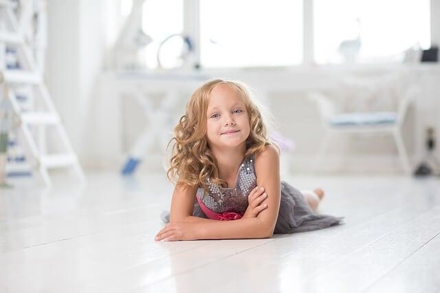 mała dziewczynka z kręconymi blond włosami w srebrnej sukience leży na jasnej podłodze w pokoju z białymi meblami