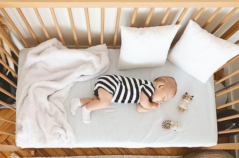Widok z góry na małe dziecko ubrane w body w biało czarne paski, leżące na białym prześcieradle przy białym kocyku i białych poduszkach i przy małych grzechotkach, w drewnianym łóżeczku