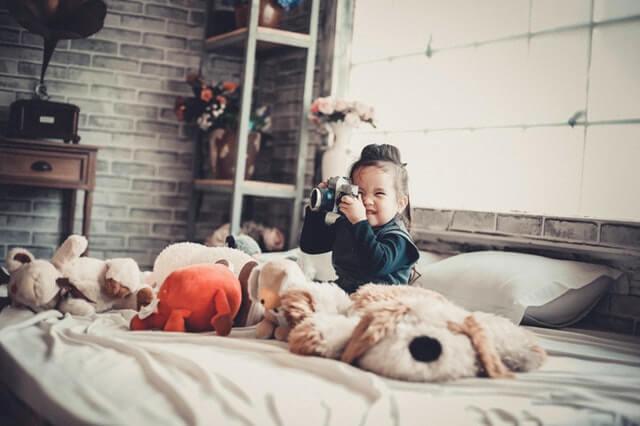 mała ciemnowłosa dziewczynka siedzi na łóżku pod oknem trzymając w ręku aparat fotograficzny, a przy niej porozrzucane są pluszowe zabawki, a przy ścianie stoi szafka i stary gramofon
