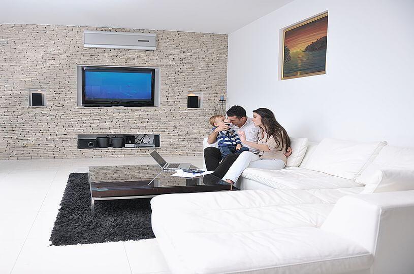 młoda kobieta ubrana w jasną bluzkę i jasne spodnie z długimi brązowymi włosami siedzi na białym narożniku w jasnym pokoju ze ścianą z jasnych cegieł na której wisi telewizor, obok mężczyzny, który na kolanach trzyma dziecko ubrane w ciemne spodnie i sweter w niebieskie paski