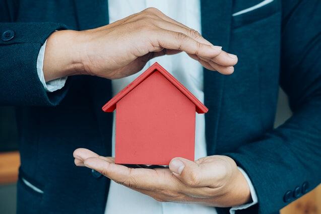 Ręką osłaniająca dom będąca synonimem monitoringu domu