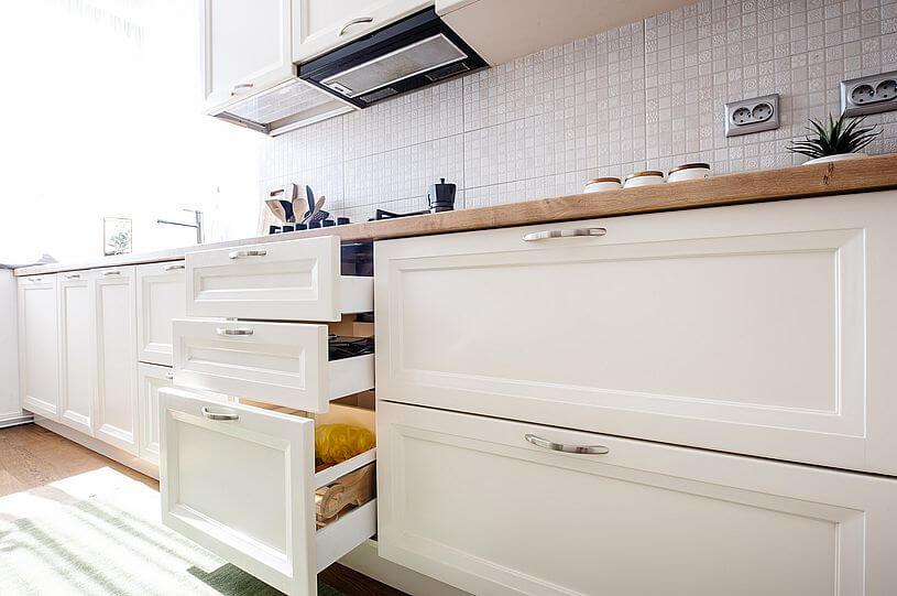 Nowoczesne domy elegancka kuchnia, czyli jasne meble w kuchni i trzy wysunięte szuflady