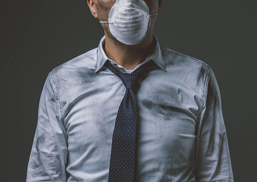 oczyszczacz powietrza, czyli mężczyzna ubrany w niebieską koszulę i niebieski krawat z maseczką na twarzy, ubrudzony czarnym kurzem, nieposiadający oczyszczacza powietrza w domu
