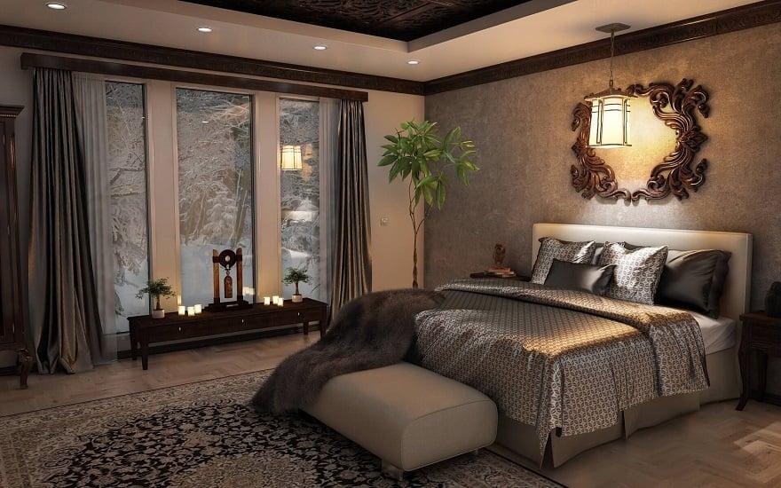 zdjęcie przytulnej sypialni z dużym łóżkiem i srebrną pościelą, jasną pufą i z dużym oknem, za którym widać zimę