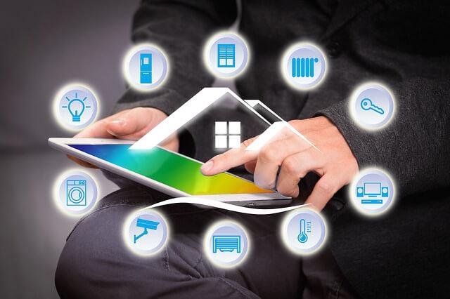 mężczyzna trzyma w ręku tablet nad którym znajdują się wirtualne ikony symbolizujące smart home czyli inteligentny dom