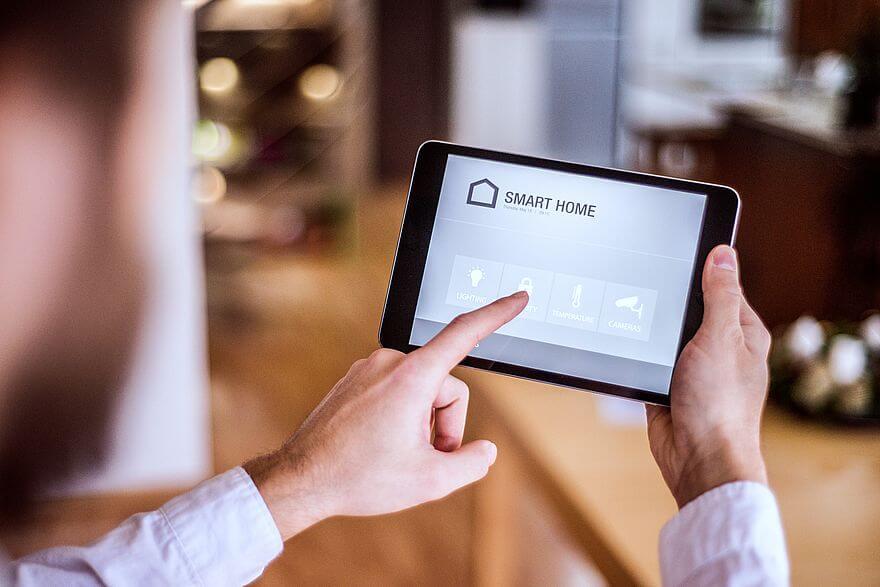 Urządzenia smart home na zimę, czyli tablet ze screenem panelu zarządzającego urządzeniami smart home w rękach mężczyzny