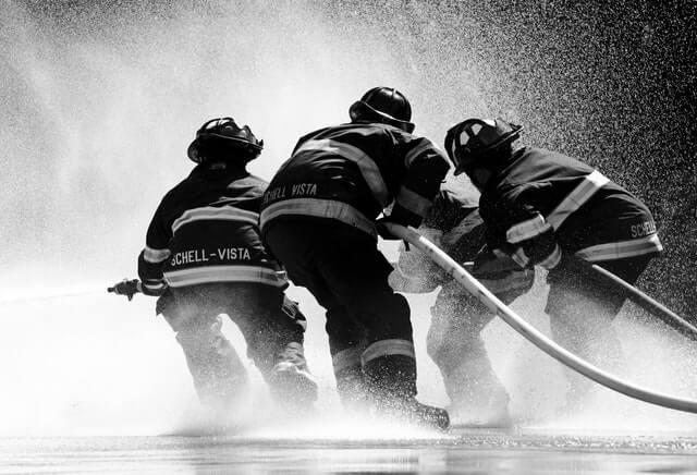 czarno-białe zdjęcie czterech strażaków ciągnących dwa węże, z których leje się duży strumień wody
