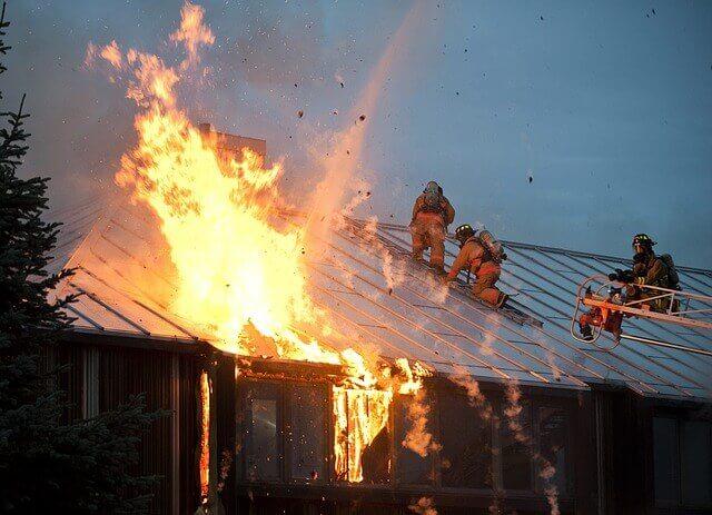 strażacy usiłujący dogasić płonący dach