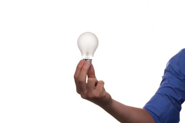ręka mężczyzny w niebieskiej koszuli trzymająca białą żarówkę