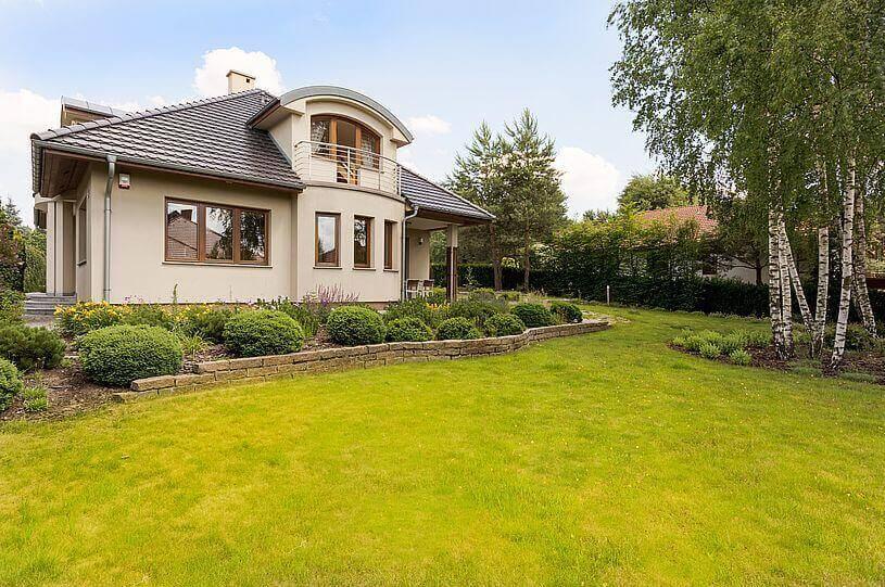 Ukryte kamery na posesji, czyli widok na dom jednorodzinny z brązową elewacją i brązowymi oknami stojący nad zieloną trawą i skalniakiem z zielonymi roślinami