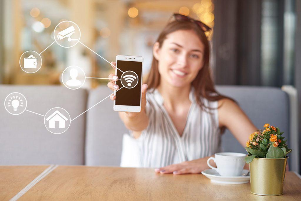 Kobieta ze smartfonem z aplikacją do ochrony domu